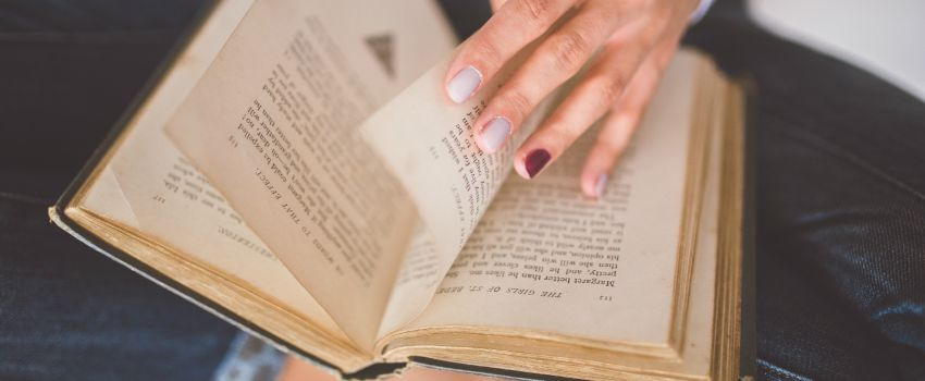 Hand turning pages in book